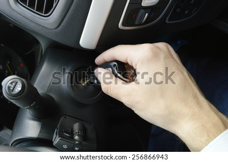 Hand holding car key for starting the car.