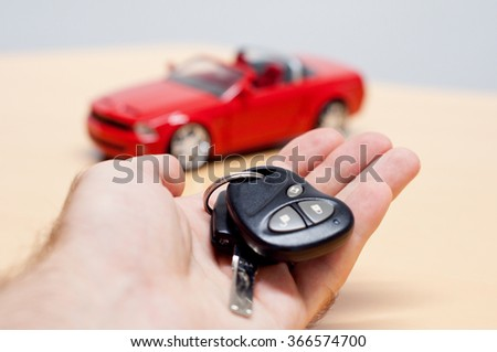 Hand holding car key with silhouette of a convertible cabriolet car in the background - stock photo