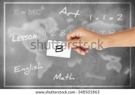 "Hand holding card with word of ""B"" chalkboard background"