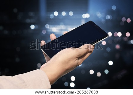 Hand holding cellphone with blank screen on blurry night city. You can put your design on the cellphone - stock photo