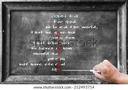 "Hand holding chalk and writing text form bible ""JOHN 3:16 For God so loved the world, that he gave his only Son, that whoever believes in him should not perish but have eternal life"" on blackboard. - stock photo"