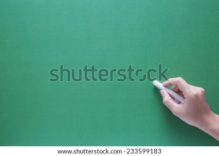 hand holding chalk on green board background
