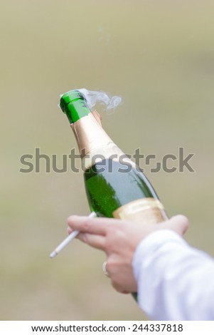 Hand holding champagne bottle and cigarette. Smoke after opening champagne bottle