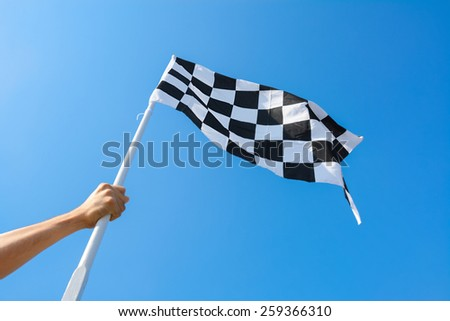 Hand holding checkered flag on blue sky background - stock photo