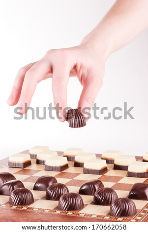 Hand holding chocolate candy over chess board with candies arranged as chess - stock photo