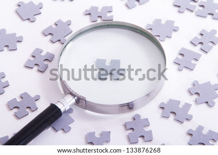 Hand holding classic style magnifying glass and searching leader puzzle piece among others on white. - stock photo