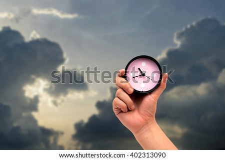 hand holding clock on dramatic sky background.