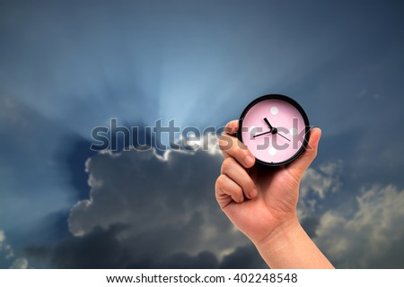 hand holding clock on sun beam and sky-clouds background.