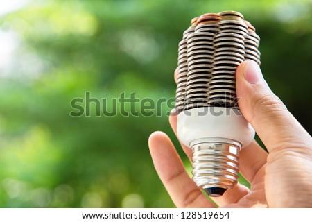 hand holding coin light bulb,energy concept - stock photo