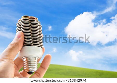 hand holding coin light bulb,energy concept  - stock photo
