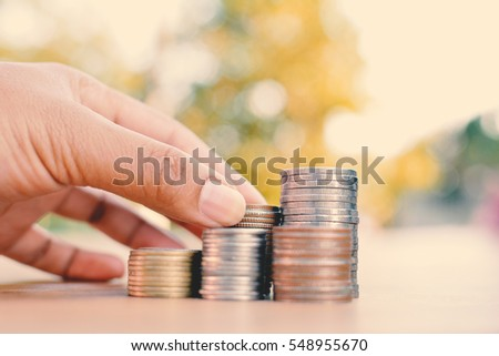 Hand holding coin on old wood tree bokeh background.color of hipster tone concept save money