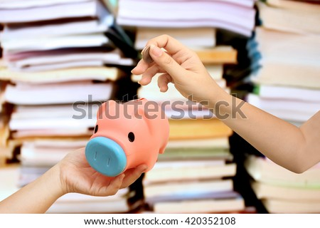 hand holding coin to piggy bank with blur stacking book background - stock photo