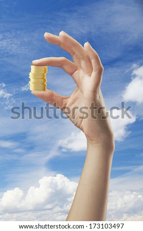 hand holding coins on a sky background