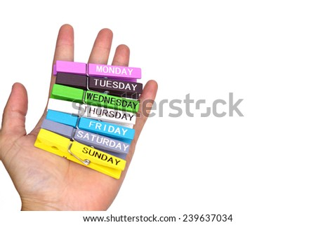 hand holding colorful wooden clips with days label