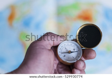 Hand holding compass in front of world map, selective focus./Hand holding compass in front of world map