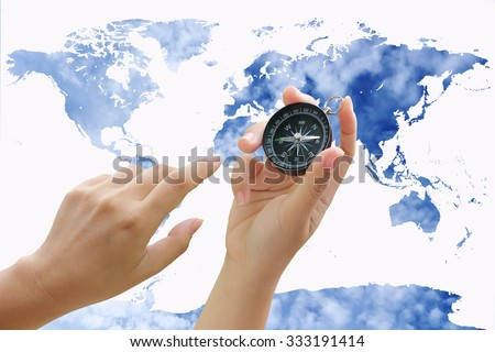 hand holding compass on world map with blur cloud spread on blue sky background - stock photo
