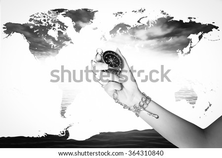 hand holding compass with world map on blur dark ocean and light background