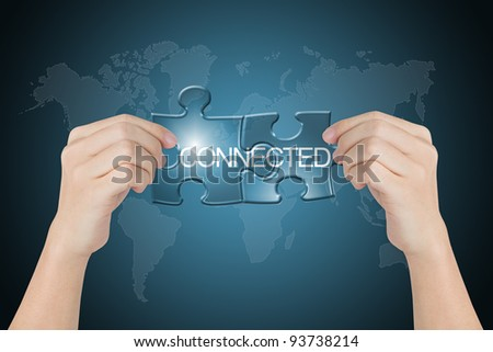 hand holding connected jigsaw puzzle with world map background - stock photo