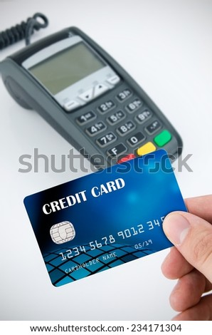 Hand holding credit card. Payment terminal in background - stock photo