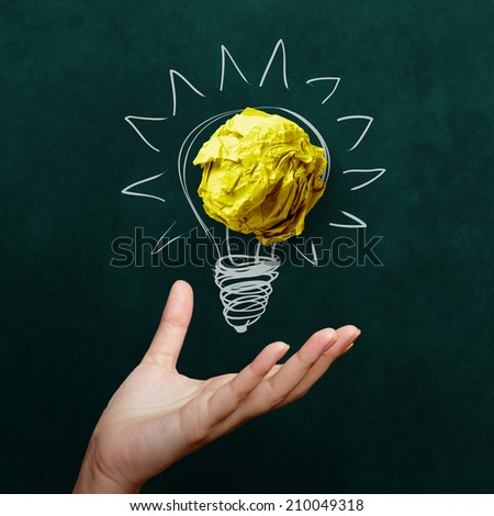hand holding crumpled paper with Light bulb on blackboard background as concept