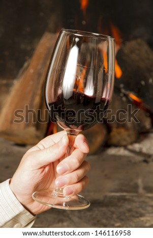 Hand holding cup of Wine by the fireplace, glasses of wine. - stock photo