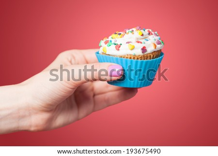 Hand holding cupcake on red background - stock photo