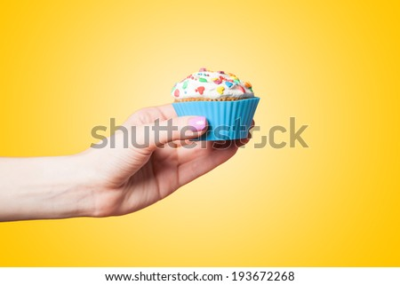 Hand holding cupcake on yellow background - stock photo