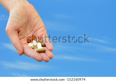 hand holding daily vitamins or medicine and blue sky