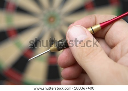Hand holding dart next to darkboard - stock photo