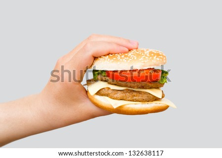 Hand holding delicious fast food cheeseburger on grey background