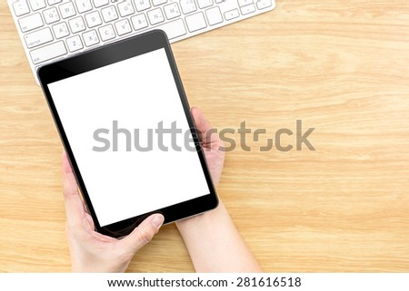 Hand holding Digital Tablet computer with empty screen and keyboard on wooden table, Mock up for adding your design, Clipping path on screen - stock photo