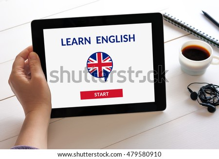 Hand holding digital tablet computer with online learn English concept on screen. All screen content is designed by me