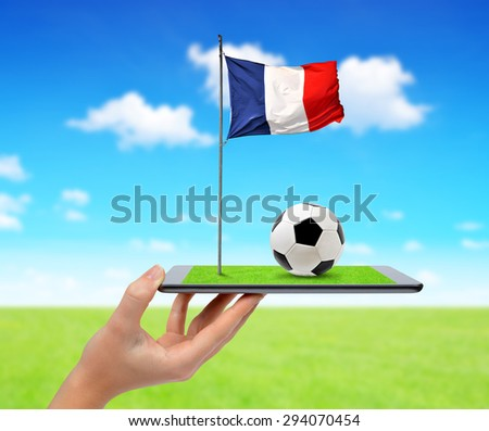 Hand holding digital tablet pc with soccer ball and French flag  - stock photo