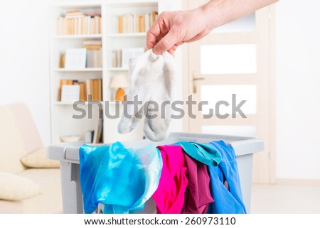 Hand holding dirty white socks over a hamper or basket - stock photo