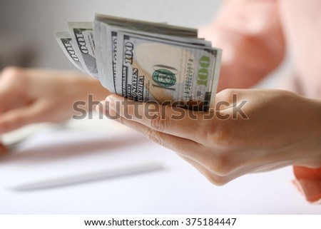 Hand holding dollar banknotes on white background