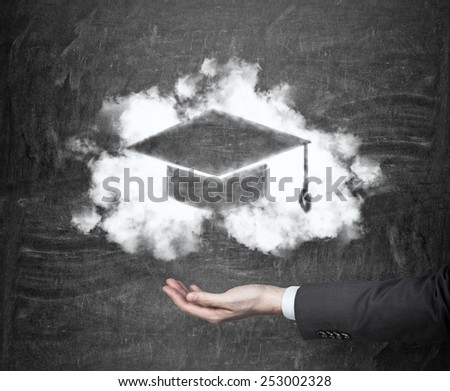 hand holding drawing bachelor hat on black background - stock photo