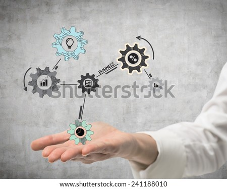 hand holding drawing cogwheel and gears, close up - stock photo