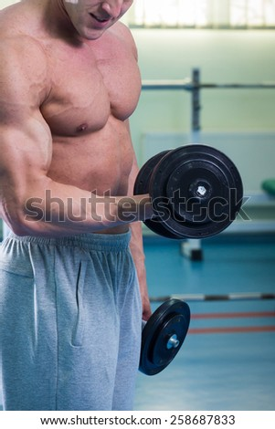 Hand holding dumbbell.Close up.Muscular arm in the gym. Training, sports, hand, dumbbell, trainnings. - The concept of a healthy lifestyle and fitness. article about fitness and sports.