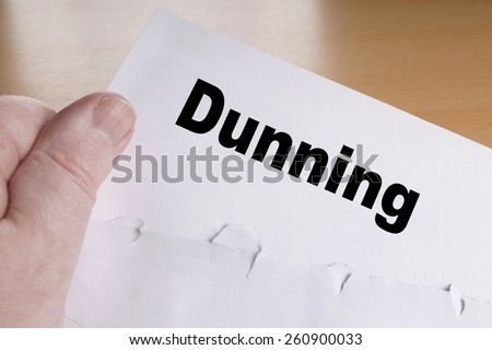 hand holding dunning letter with opened envelope