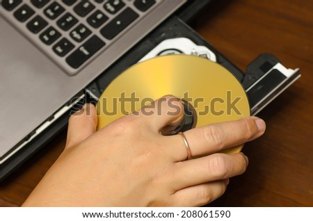 hand holding dvd insert to notebook computer - stock photo