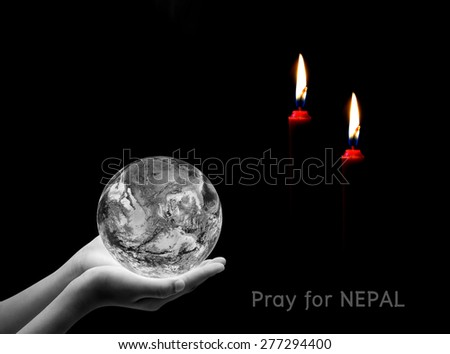 Hand holding earth and candle on black background , Pray for nepal ,  Elements of image are furnished by NASA - stock photo