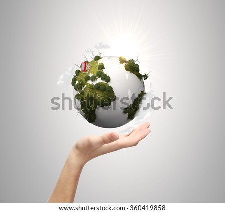 hand holding earth on gray background - stock photo