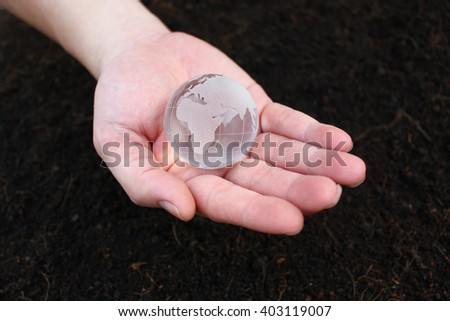 Hand holding earth with soil background