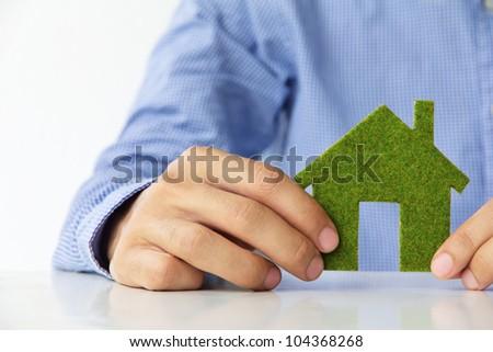 Hand holding eco house icon - stock photo