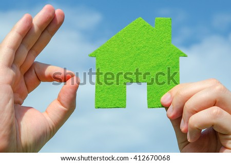 Hand holding eco house icon concept and other hand showing ok sign on the blue sky with clouds background - stock photo