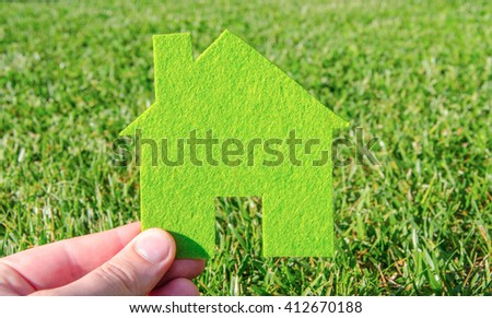 Hand holding eco house icon concept on the green grass background - stock photo