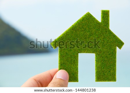 Hand holding eco house icon with nature background