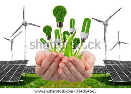 Hand holding eco lightbulbs. In the background solar energy panels and wind turbine. Clean energy concept. - stock photo