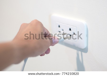 Hand holding electric plug into Electricity Socket on clean cement wall background