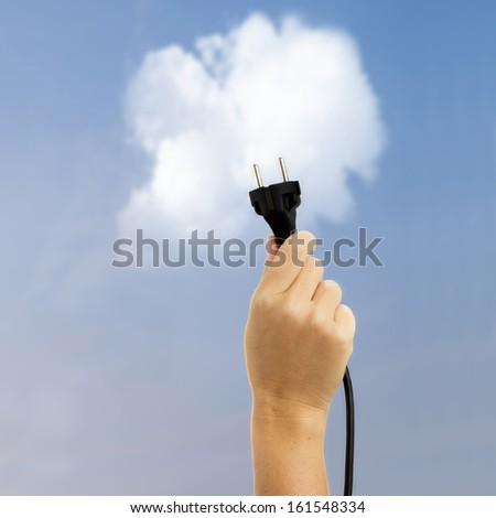 hand holding electric plug on blue sky with cloud background, clean alternative energy concept